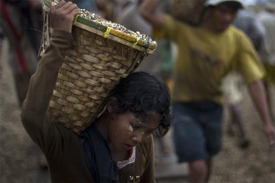 Un niños transporta un cesto lleno de piedras descargando un barco junto a trabajadores adultos en un puerto en Yangon, Myanmar,el paso año. Según las Naciones Unidas más de un tercio de los niños del país trabajan como adultos
