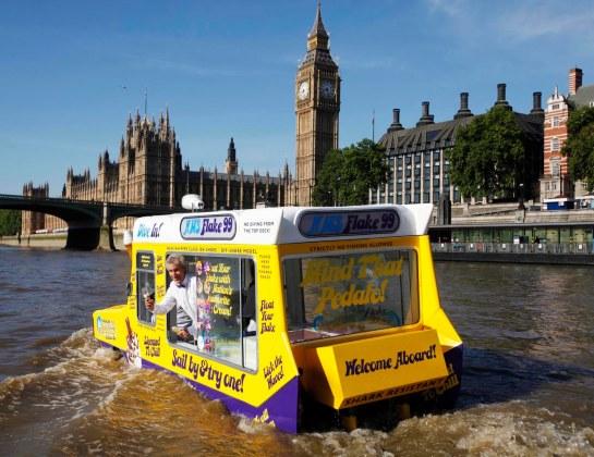 """Jamie Campbell, a bordo del H.M.S. """"Flake 99"""", la primera furgoneta de helados anfibia del mundo, en pose más propia de agente especial que de heladero, surcando las aguas del Támesis. foto: ©David Parry/PA"""